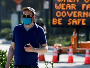 A pedestrian wearing a face mask walking in front of a sign that asks people to be safe